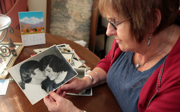 Lynda Mathews holding her photo with John Lennon, her second cousin.