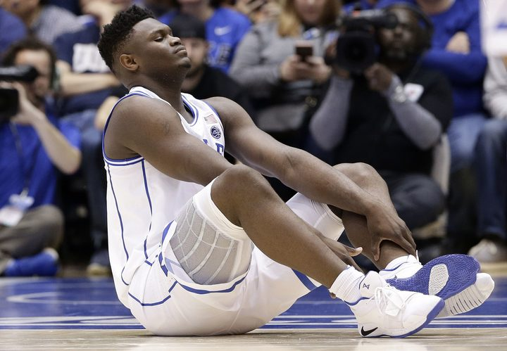 Duke's Zion Williamson sits on the floor following a injury during the first half of an NCAA college basketball game against North Carolina