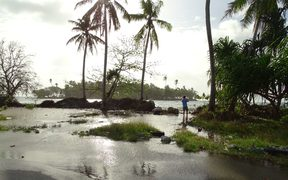 Atoll nations are seeing an increased frequency in ocean inundations during high tides and storms. In this 2016 file photo of Majuro Atoll, a photographer stands ankle deep in water as ocean water floods over the island and onto the main road in the foreground.
