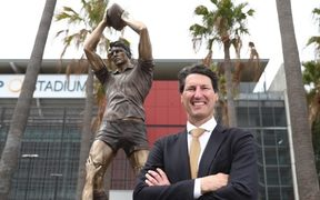 John Eales in front of the statue in his honour at Suncorp Stadium.