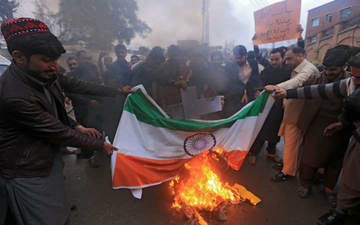 Pakistani protesters burn an Indian national flag during a protest in Peshawar on February 26, 2019, following the Indian Air Force strike launched on a Jaish-e-Mohammad camp at Balakot.