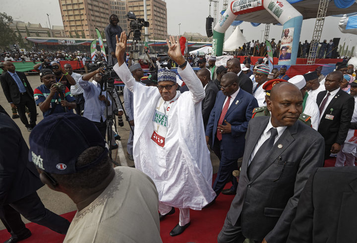 FILE - In this Wednesday, Feb. 13, 2019 file photo, incumbent President Muhammadu Buhari gestures to supporters at a campaign rally in Abuja, Nigeria.