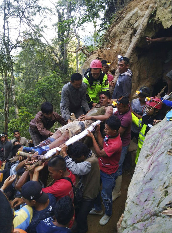 In this undated photo released by Indonesian Search And Rescue Agency (BASARNAS) rescuers evacuate a survivor from inside of a collapsed gold mine in Bolaang Mongondow, North Sulawesi, Indonesia.