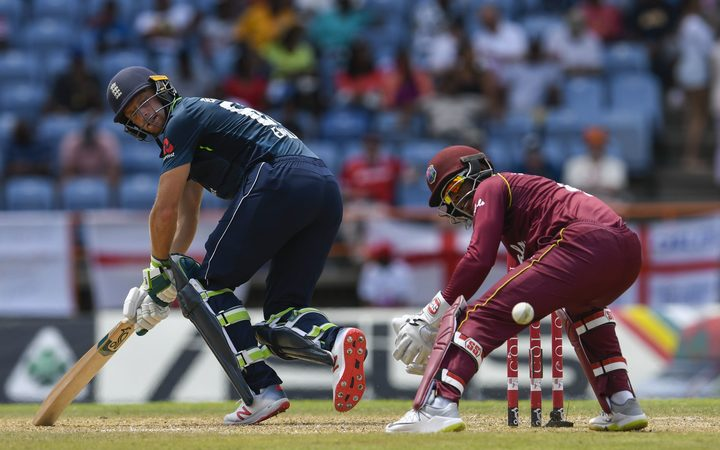 Jos Buttler (L) of England hits past Shai Hope (R) of West Indies during the 4th ODI between West Indies and England at Grenada National Cricket Stadium.