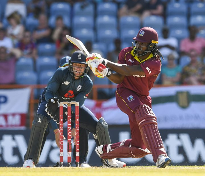 Chris Gayle (R) of West Indies hits a four as Jos Buttler (L) of England watches during the 4th ODI between West Indies and England in Grenada.