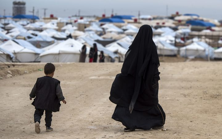 A displaced Syrian woman and a child walk toward tents at the Internally Displaced Persons (IDP) camp of al-Hol