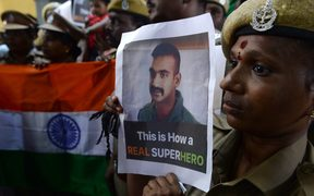 Indian security forces pose with the national flag and pictures of Indian Air Force pilot Abhinandan Varthaman during an event to pray for his return