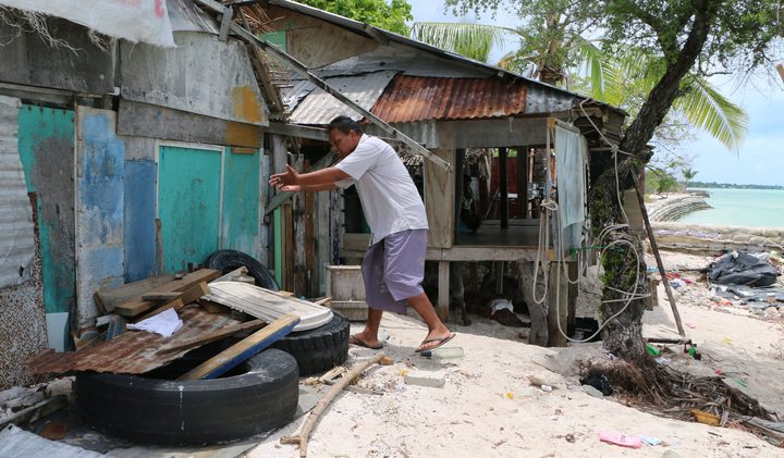 Maerere Eria shows how the water surges through his house during king tides
