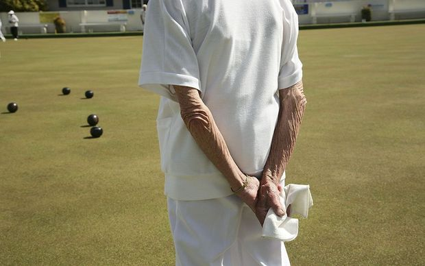 Elderly person playing lawn bowls