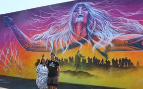 Amiria Puia-Taylor and Bobby MacDonald in front of the Onehunga mural.