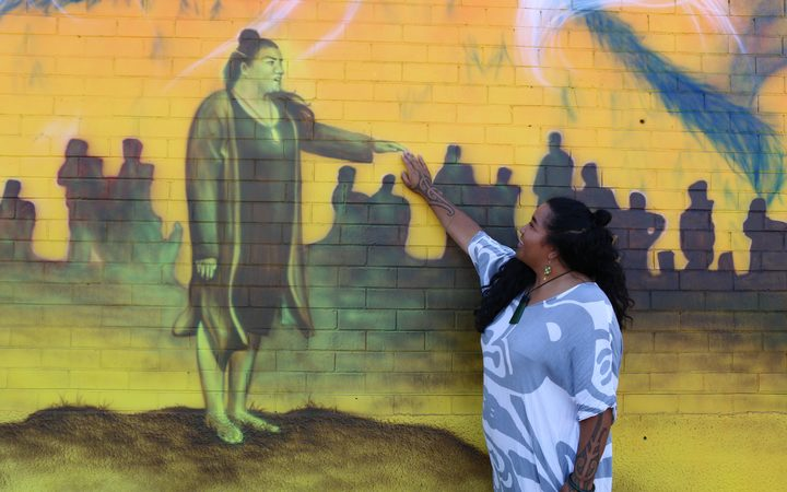 Amiria Puia-Taylor reaches out to the image of her on the mural.