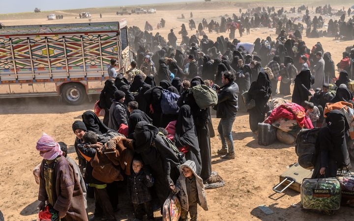 Women and children evacuated from the Islamic State (IS) group's embattled holdout of Baghouz arrive at a screening area held by the US-backed Kurdish-led Syrian Democratic Forces (SDF)