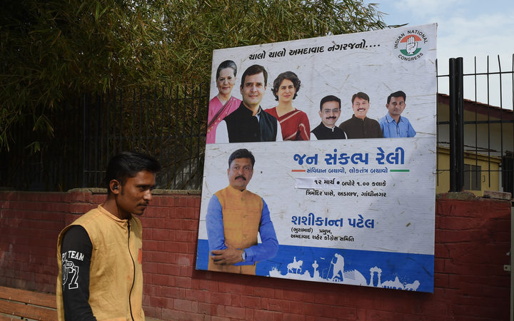 An Indian man walks in front of a billboard depicting India's Congress Party president Rahul Gandhi