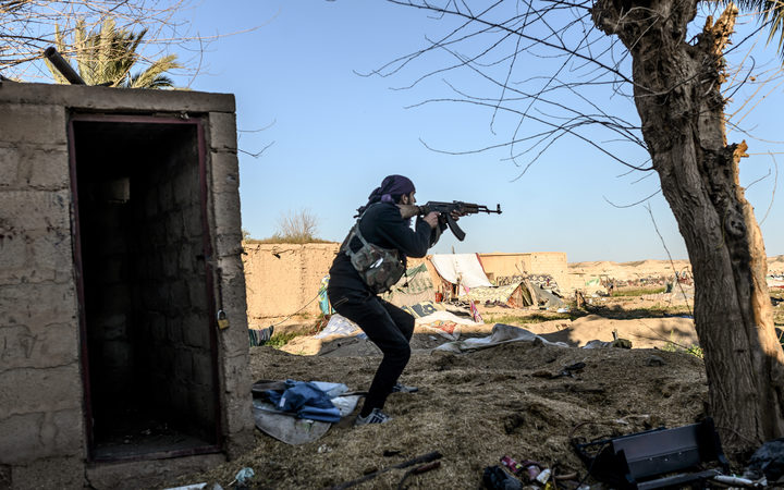 A fighter with the Syrian Democratic Forces (SDF) takes aim with his Kalashnikov assault rifle after seeing a man walking towards his position in the town of Baghouz