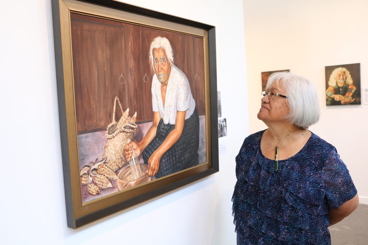 Rovina Tata next to the portrait of her Kuia Makarita Hose.