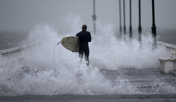 A surfer makes his way along the pier before jumping off into Port Phillip Bay as the storm lashes the Melbourne area.