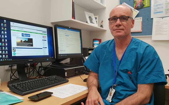 Wellington Cardiologist, Dr Andrew Aitken,  in hospital scrubs sitting in his office