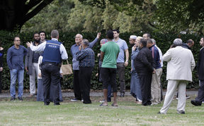 Police talk to witnesses near a mosque in central Christchurch, New Zealand, Friday, March 15, 2019.