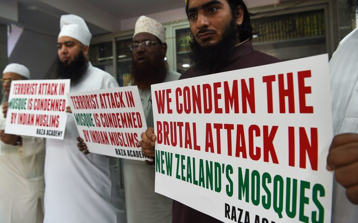 Indian Muslims and clerics in Mumbai hold posters to condemn the shooting.