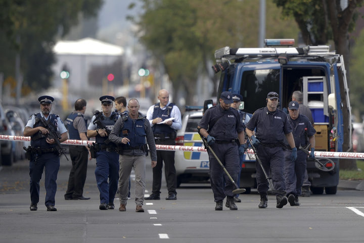 Police officers search the area near the Al Noor mosque, site of one of the mass shootings at two mosques in Christchurch, New Zealand, Saturday, March 16, 2019.