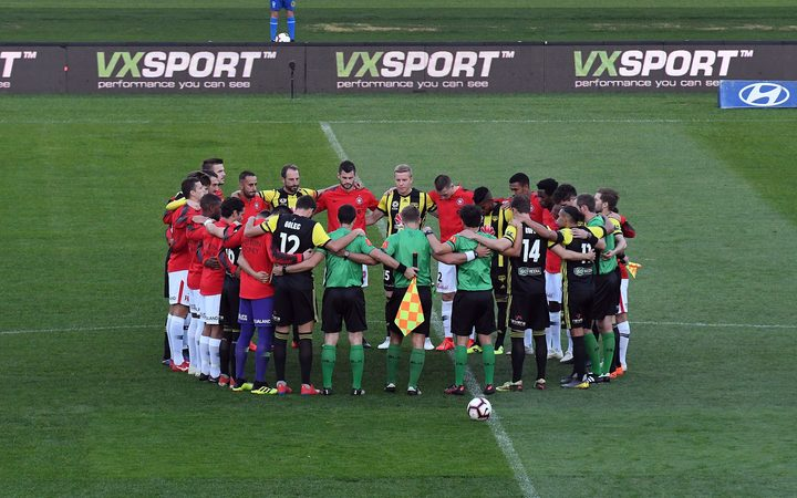 Players of Wellington Pheonix and Western Sydney Wanderers huddleup in silence in memory of the Christchurch victims during the A-League game in Wellington.