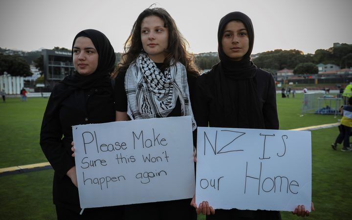 Three young women and their signs at the Basin Reserve vigil in Wellington  for the victims of the Christchurch terror attack