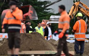 Representatives of the Muslim community and workers prepare grave sites for victims in Christchurch.