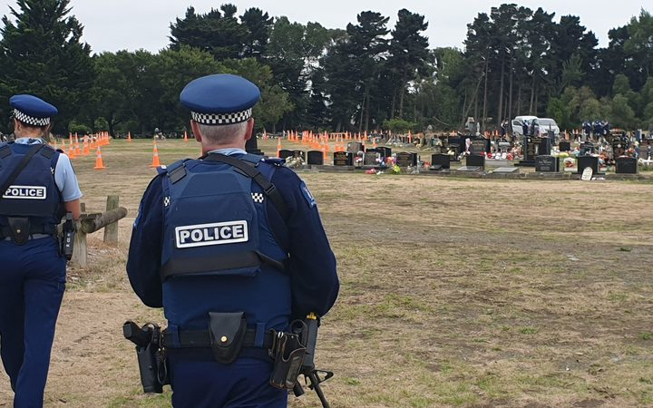 Armed police stand guard as Memorial Park Cemetery is prepared for the burial of victims of the Christchurch mass shooting.