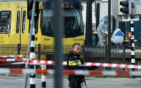 Police officer and forensic investigators near  near a tram in Utrecht where a gunman opened fire killing three people.