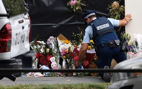A police officer lays flowers at the Al Noor mosque.