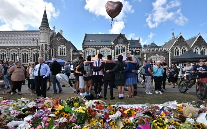 A group of students sing in front of flowers left in tribute to victims of Friday's attacks at the Botanical Garden in Christchurch.