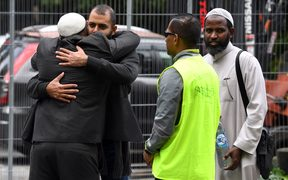 A member of the Jewish community embraces a member of the Muslim community at the Hagley Ovel makeshift information center in Christchurch.