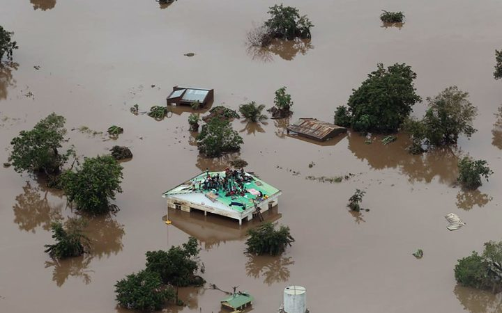 People on a roof surrounded by flooding in Beira region.