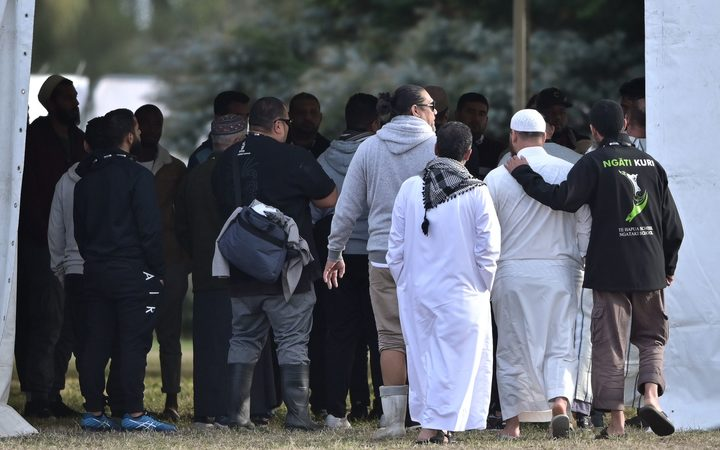 People gather at the cemetery as funerals for victims of the mosque attack are due to take place.