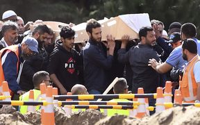 Mourners carry the first coffins of victims killed in the mosque attacks during a funeral at the Memorial Park cemetery in Christchurch