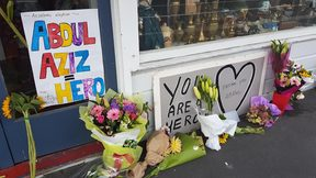 Floral tributes and signs are building up outside the shop of Abdul Aziz, who threw an eftpos machine at the attacker.