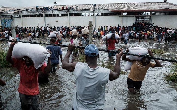 """People looting sacks of Chinese rice printed """"China Aid"""" from a warehouse surrounded in Beira, Mozambique."""
