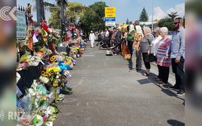 People link arms around NZ mosques during Friday prayers