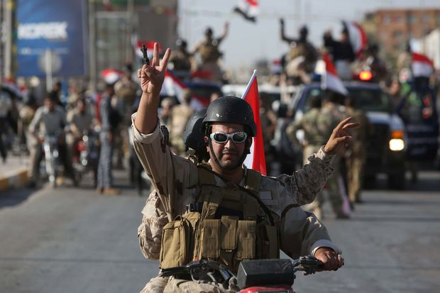 Members of the Al-Abbas brigades, aligned with the Iraqi government, parade in Karbala.