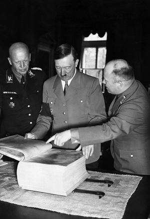Adolf Hitler looks at an edition of Mein Kampf published on parchment.