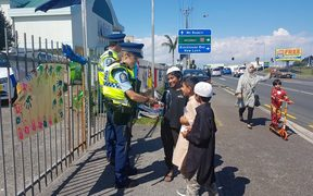 Young boys get autographs from police outside the Masjid e Umar Mosque in Auckland, where Prime Minister Jacinda Ardern spoke today.
