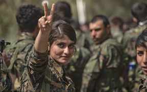 A female fighter of the US-backed Kurdish-led Syrian Democratic Forces (SDF) flashes the victory gesture