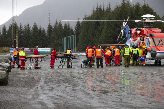 Rescuers wait to assist stranded passengers who were airlifted by helicopter from the cruise ship Viking Sky on March 24, 2019 in Hustadvika on the west coast of Norway near Romsdal.