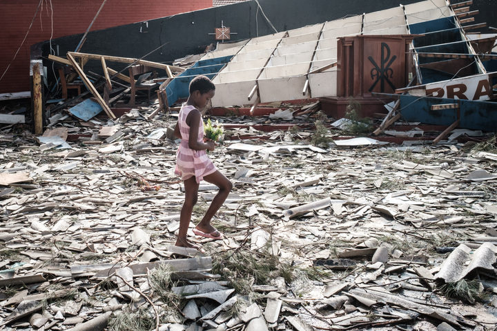 A girl collects artificial flowers from the rubble of a building destroyed by the cyclone Idai at Sacred Heart Catholic Church in Beira, Mozambique.