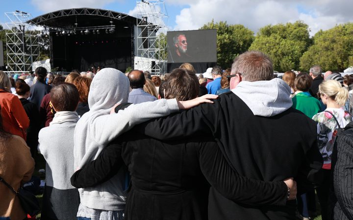 People stand while Yusuf Islam / Cat Stevens sings during the national remembrance service in Christchurch.