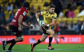 Hurricanes first five Beauden Barrett comes under pressure from Crusaders captain Sam Whitelock.