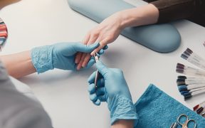 Nail artist creating manicure in beauty salon