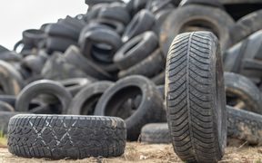 A stack of tires on an old garbage dump. Old worn out tires piled up. Season of the autumn.