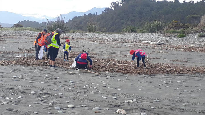 South Westland Coastal Cleanup volunteers helping clear litter and detritus swept into rivers and beaches from a disused landfill after the storm.