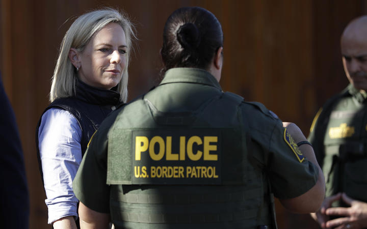 US Department of Homeland Security Secretary Kirstjen Nielsen, left, speaks with Border Patrol agents near a newly fortified border wall structure in Calexico, Calif.